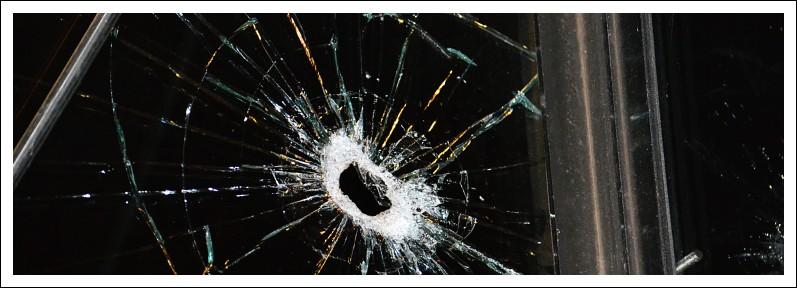 Das Bild zeigt ein Loch in einer gesplitterten Scheibe
