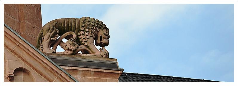 Das Bild zeigt eine mit einer Schlange kämpfende Löwenfigur am Ostchor des Doms