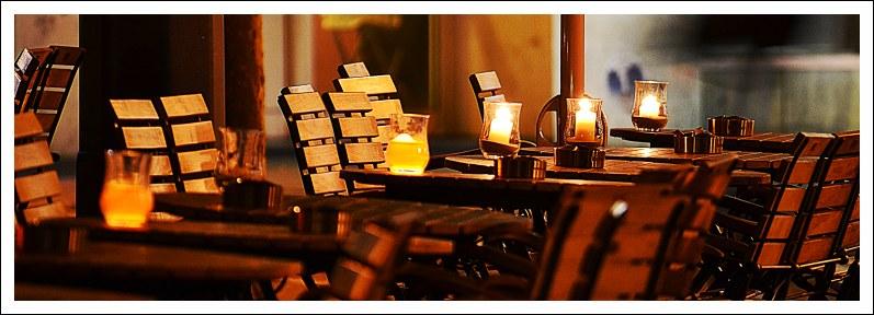 Das Bild zeigt Tischleuchten einer Gaststätte am abendlichen Bahnhofsplatz