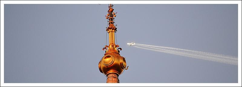 Das Bild zeigt die Turmspitze des Doms und ein Düsenflugzeug