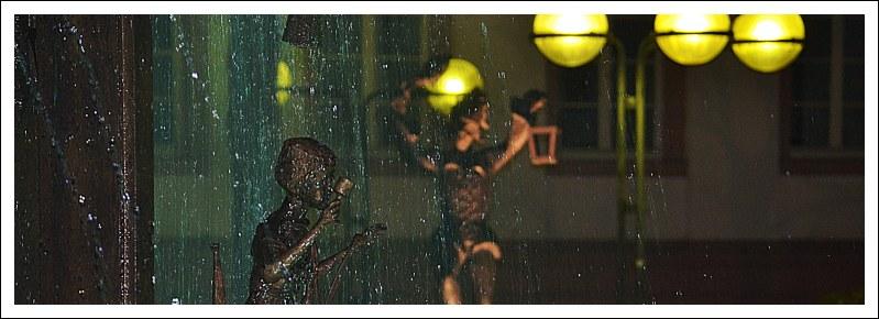 Das Bild zeigt eine Figur vom Fastnachtsbrunnen und im Hintergrund eine Narrenfigur