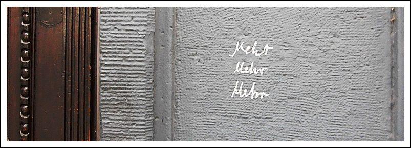 """Das Bild zeigt eine Hauswand mit dem Sgraffito """"mehr mehr mehr"""""""