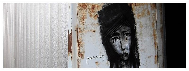 Das Bild zeigt ein Graffito mit einem aus schwarzer Farbe gesprühten Frauenporträt, dessen Augen wie Tränen verlaufen