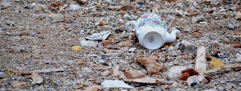 Das Bild zeigt eine angeschlagene Kaffeekanne auf einem Schotterfeld