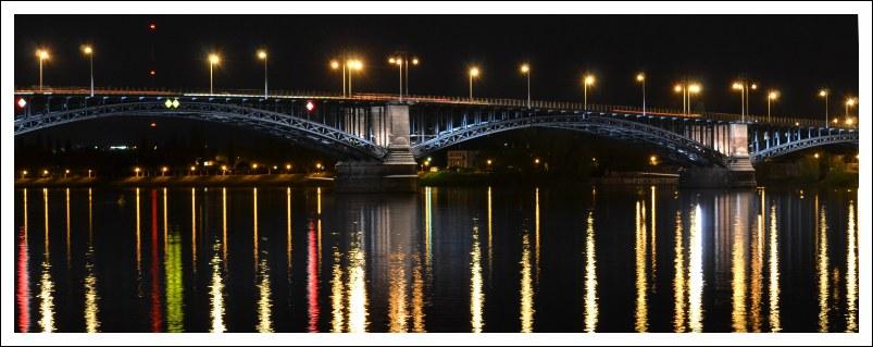 Das Bild zeigt eine Nachtansicht der beleuchteten Theodor-Heuss-Brücke