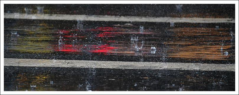Das Bild zeigt Regentropfen auf dem Asphalt