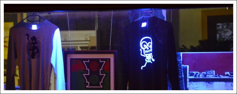 Das Foto zeigt einen stilisierten Totenkopf mit Knochenmännchen in Leuchtfarbe auf einem schwarzen Hemd in der Auslage eines Schaufensters