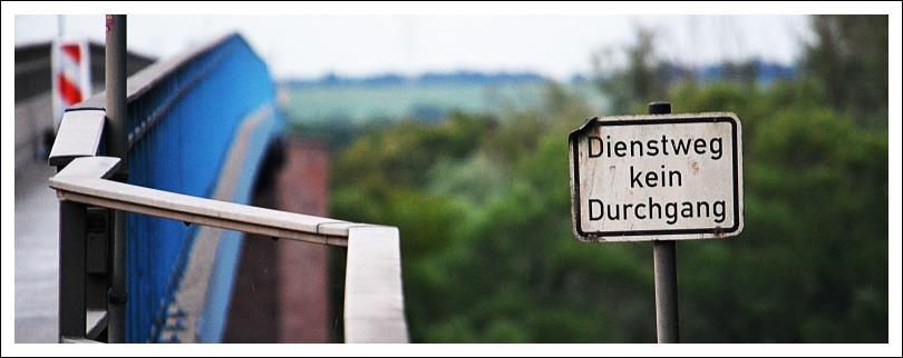 Das Foto zeigt ein Hinweischild am Rand der Autobahnbrücke Weisenau