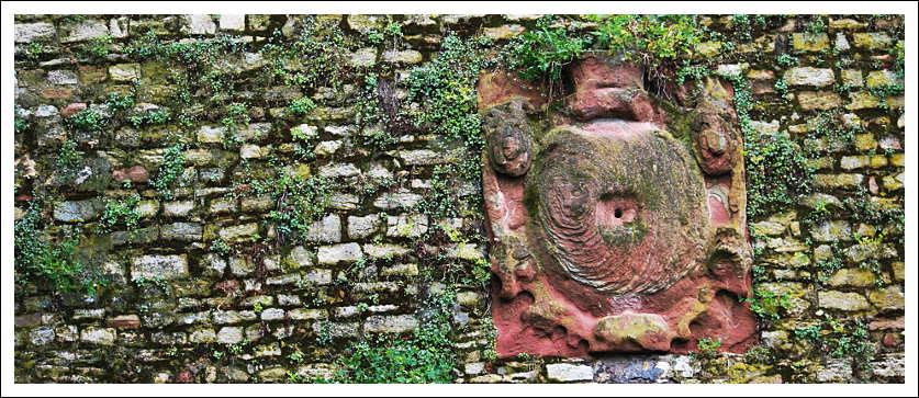 Das Foto zeigt einen verwitterten Wappenstein im Mauerwerk der Bastion Alexander